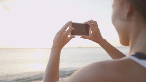 Woman taking picture using smartphone beach sunset Footage