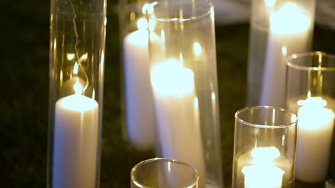 Closeup Romantic burning white candles in glass vases standing on a grass for an Live Action