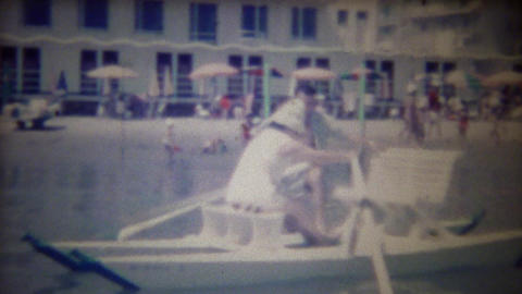 1963: Women rows beach pleasure boat man rides in comfort Footage