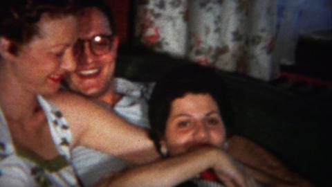 1964: Drunk man puts arm around unsure pretty women Footage
