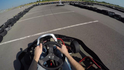 Man drives go kart on track very fast, filmed from the driver's view, man holds Footage