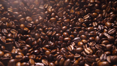 Coffee beans falling down on a a pile of smoking roasted coffee beans Footage
