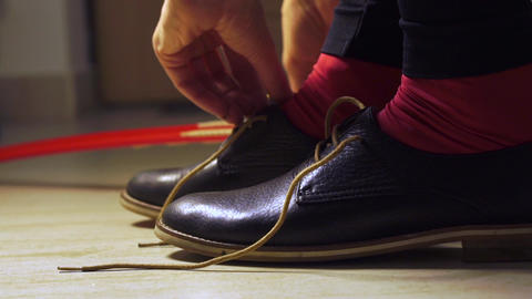Girl in red socks putting on dark shoes with a shoehorn Footage