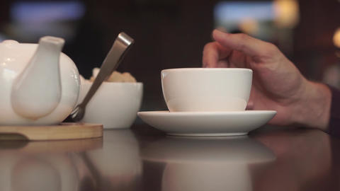 A man with a mobile phone drinking green tea in a cafe Live Action