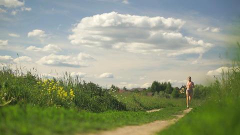 Beautiful girl running across the summer field Footage
