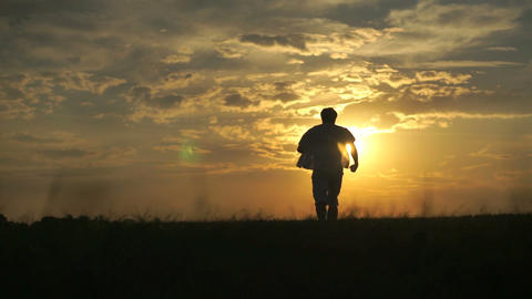 Silhouette of man running towards beautiful sunset Footage