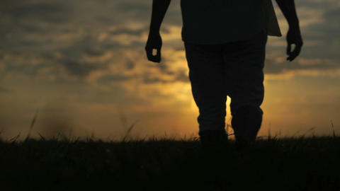 Man walking in the field with beautiful sunset on a... Stock Video Footage