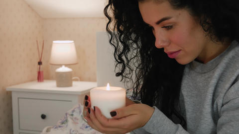 Woman holding a candle on the bed Footage