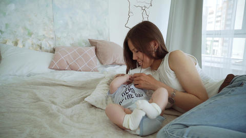 Young cute girl playing with her son on the bed. A young mother is playing with Footage