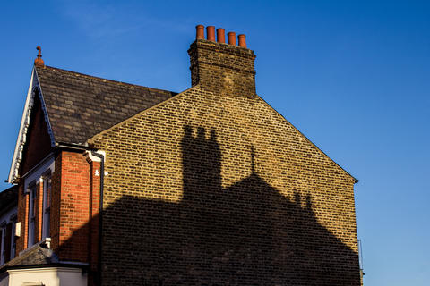 Traditional victorian brick house style with chimney on clear blue sky in London フォト