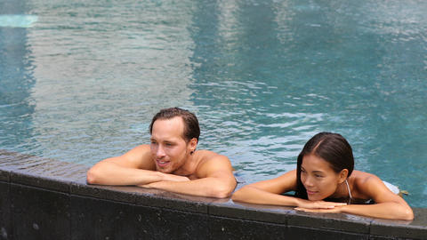 Honeymoon couple relaxing together - swimming pool Live Action