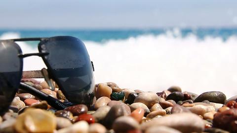 Sunglasses on a pebble beach by the sea Footage