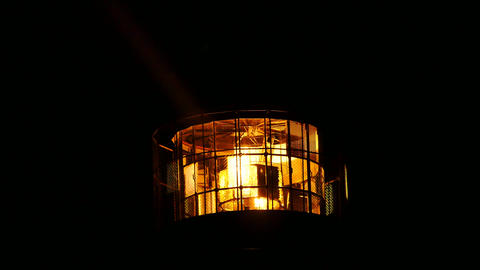 Detail of turning lamp in lighthouse. Detail of Fresnel lens. Tower illuminated Live Action