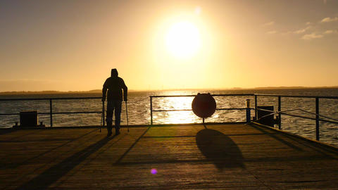 Tourist with medicine crutch goes on the wooden pier in the sunrise. Smooth Bild