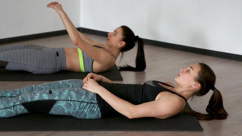 In the gym during the pilates exercise lying on the gym mats two girls lying on Footage