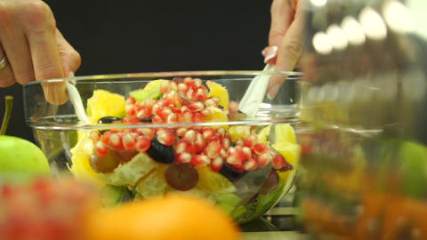 Beautiful girl hands mixing fruit salad in a glass bowl Live Action
