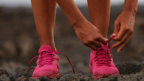 Running woman tying shoe laces going running - girl trail runner Footage