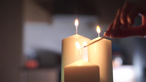 Girl hand lighting up three candles Footage