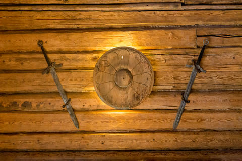 Viking swords and small shield hanging on wooden wall Photo