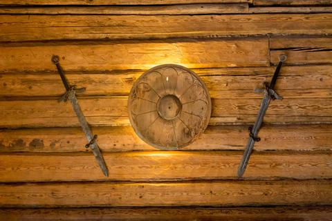 Viking swords and small shield hanging on wooden wall Fotografía