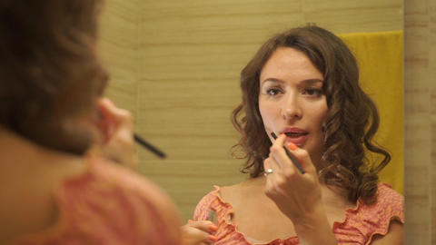 Beautiful girl in a pink dress putting a lipstick on her lips by the mirror Footage