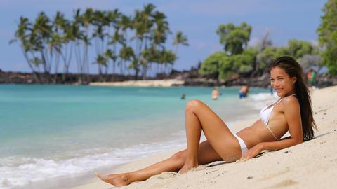 Sunbathing suntan bikini woman relaxing on beach vacation on white sand Footage