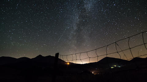 Starry night sky with milky way galaxy time lapse. Dolly shot over fence Footage