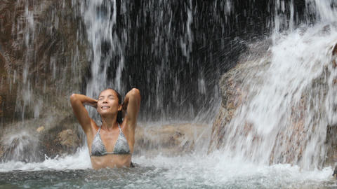 Waterfall with girl in bikini bathing and swimming in vacation travel Footage