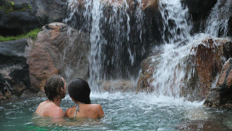 Couple bathing by waterfall in embracing and hugging romantic Footage