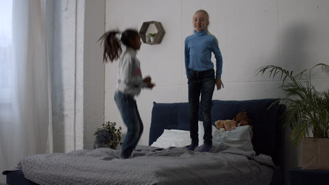Positive multi ethnic kids jumping on the bed Footage