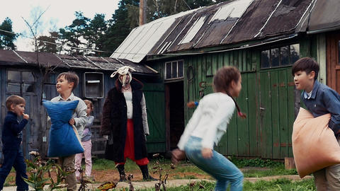 Kids fight pillows in yard of country house. Childhood. Men in costumes. Jumps Live Action