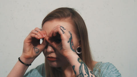 Pretty young girl in gray shirt with ear flesh tunnels use hands as binoculars Live Action