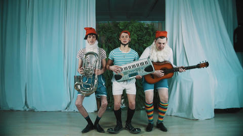 Three men dressed as gnomes with musical instruments jumps and playing music Live Action