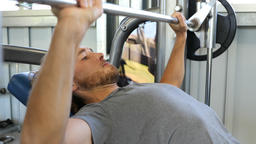 Fitness man in gym training chest muscles doing flat bench press with barbell Footage