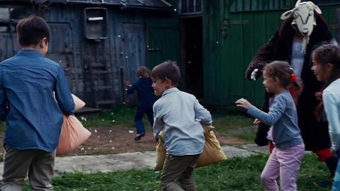Kids fight pillow in yard of country house. Countryside. Entertainment. Feathers Footage