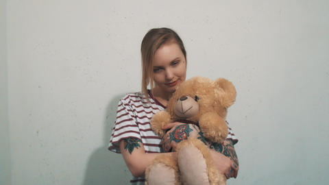 Cute blonde woman in striped shirt with tattoos, cuddling with teddy bear toy Footage