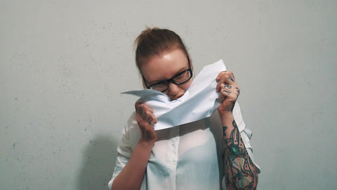 Attractive woman in white shirt, with ear flesh tunnels eating sheet of paper Live Action