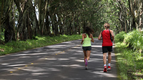 Runners running on forest road Footage