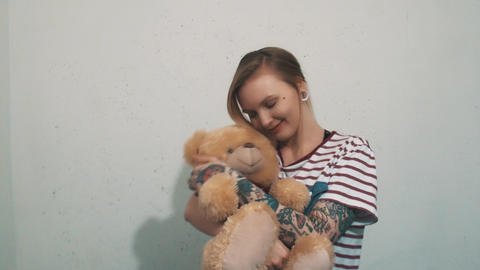 Cute blonde girl in striped shirt with tattoos, hugging with teddy bear toy Footage