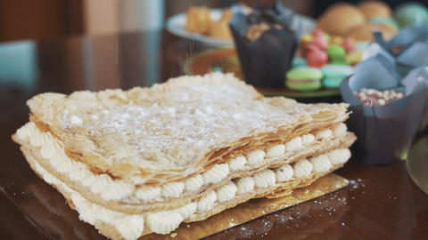 Sugar powder strew on layered cake on table with lots of pastry products Footage