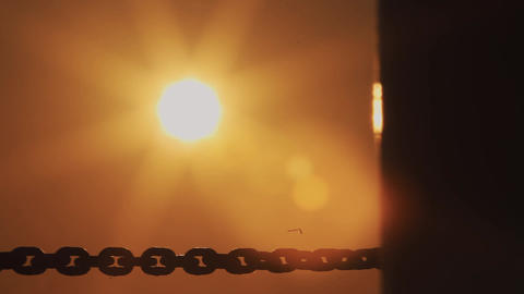 Iron black chain stretched under orange setting sun, lens flare Footage