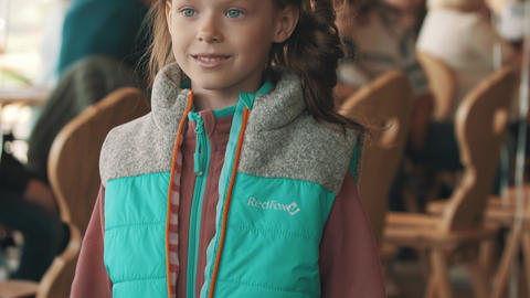 Preteen girl standing on podium showing winter clothes at kids fashion show Live Action
