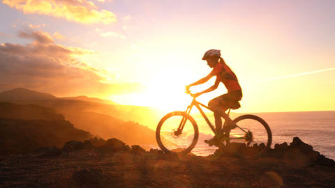 Mountain biking MTB cyclist woman cycling on bike trail at sunset by ocean Live Action