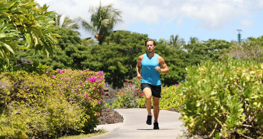 Runner man running on park path exercising on beautiful summer day Footage