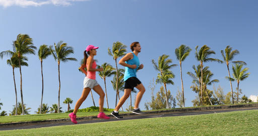People running exercising on path in beautiful neighborhood with palm trees Footage