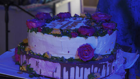 People ride huge cake with flowers and sign. Celebration. Event. Sweets. Holiday Live Action