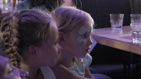 Two blonde teen girls take selfie with father. Painted faces. Children event Footage