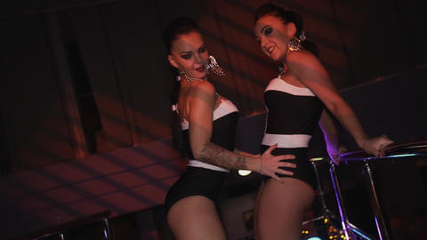 Two go go girls in black bikini sexy dance together on stand in nightclub Live Action