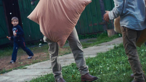 Kids play with pillows in yard of country house. Flying feathers. Men in costume Footage