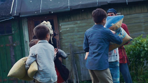 Kids fight pillows in yard of country house. Feathers fly. Man play balalaika Footage